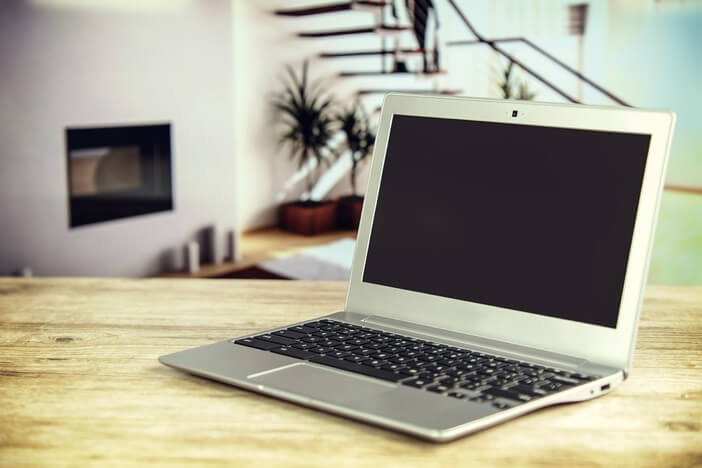 Laptop sitting on top of a wooden desk in a luxury corporate apartment